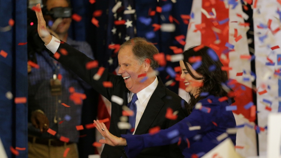 Democratic Alabama US Senate candidate Doug Jones and wife Louise smile and celebrate as red, white and blue confetti falls.