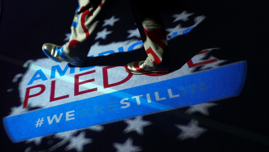 "A man walks over a projection on the floor reading ""America's pledge #wearestillin"""