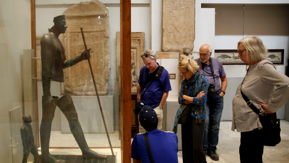 Visitors walk around pharaonic artefacts inside the Egyptian Museum