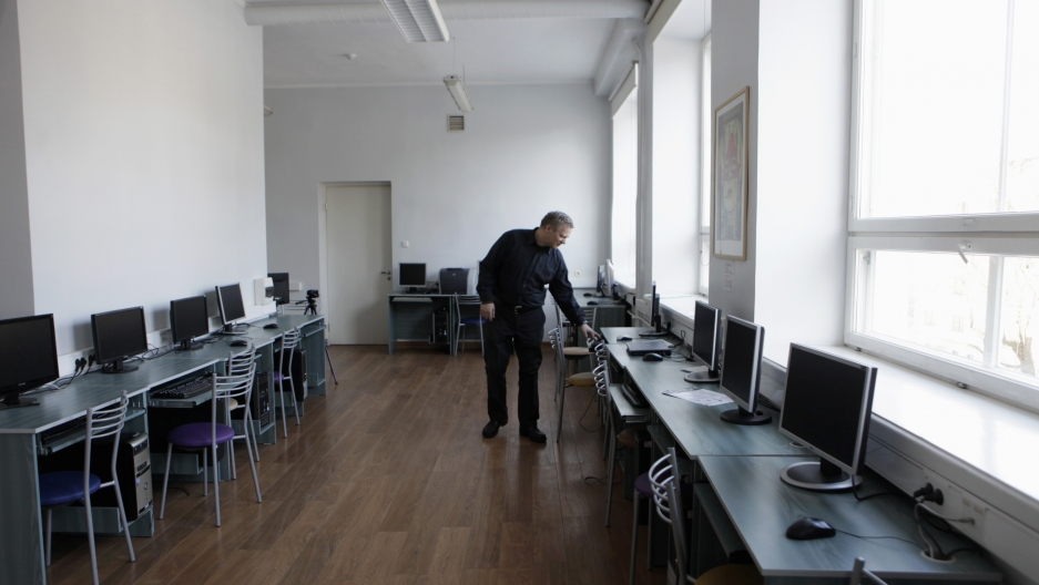 Informatics teacher Jevgeni Mihhailov inspects computers in an empty classroom in a school in Tallinn, Estonia, on March 7, 2012.