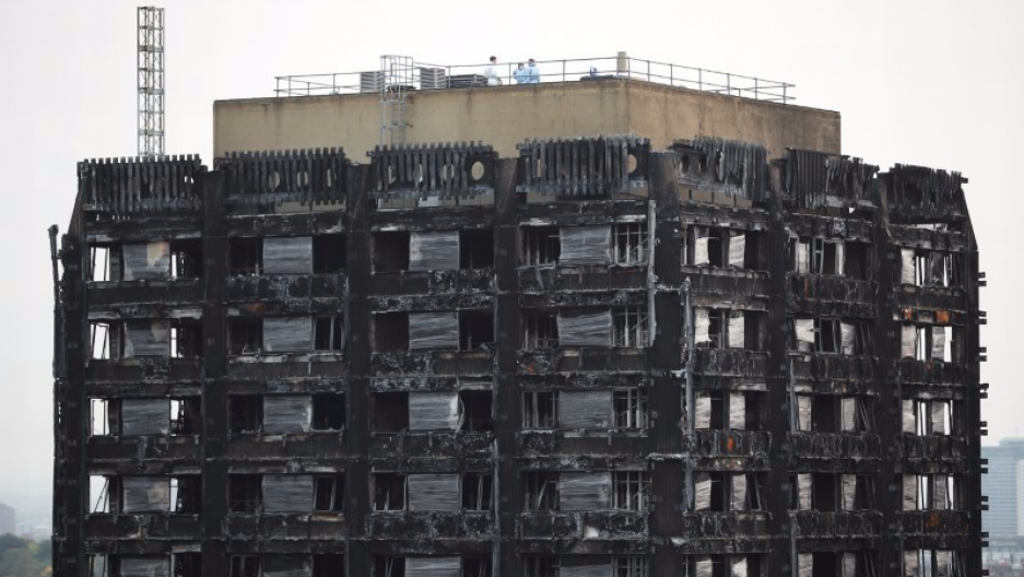 Workers stand on the roof of the burned-out remains of the Grenfell tower in London, Britain, Oct. 16, 2017.