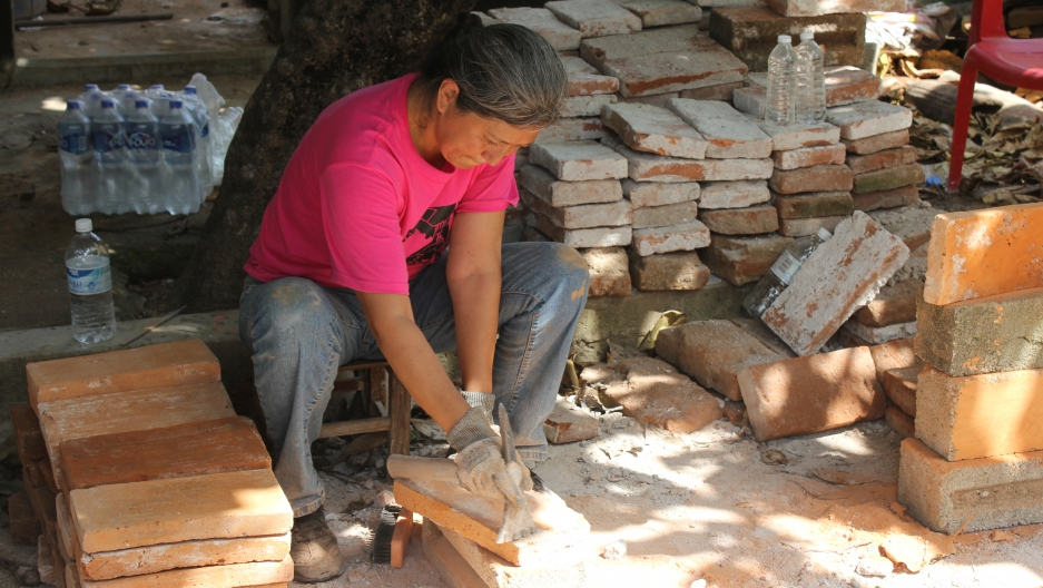 A woman scrapes mortar off of a salvaged brick with a flat end of a chisel so the brick can be reused.