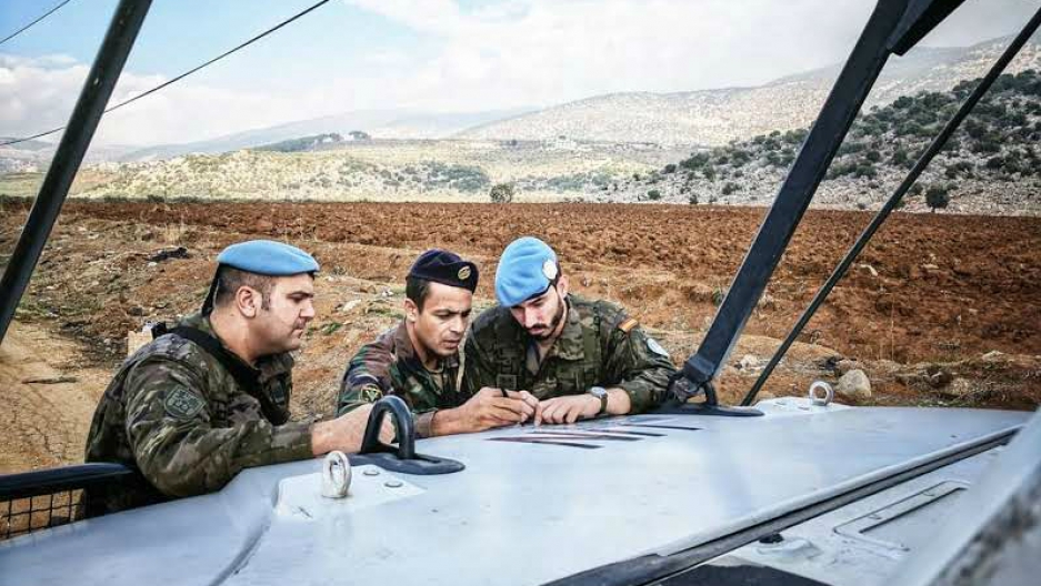 A Lebanese army soldier and two UNIFIL peacekeepers discuss the route of their joint patrol near the Lebanon-Israel border, Nov. 29, 2017.