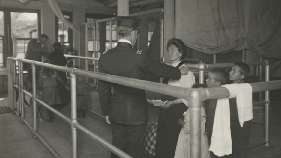 A black and white historical photo of a uniformed man with his hand on a woman's shoulder while young boys look on.