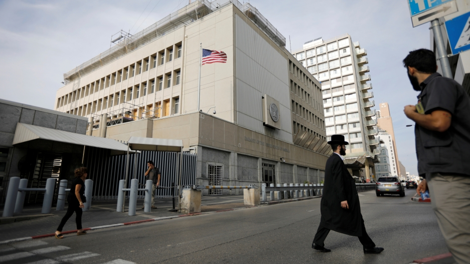 People walk past the US Embassy in Tel Aviv, Israel, Dec. 5, 2017.