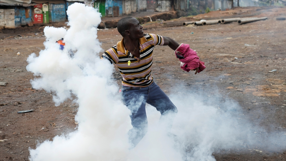 An opposition supporter returns a teargas canister fired by police during clashes in Kibera slum in Nairobi, Kenya, Oct. 26, 2017.
