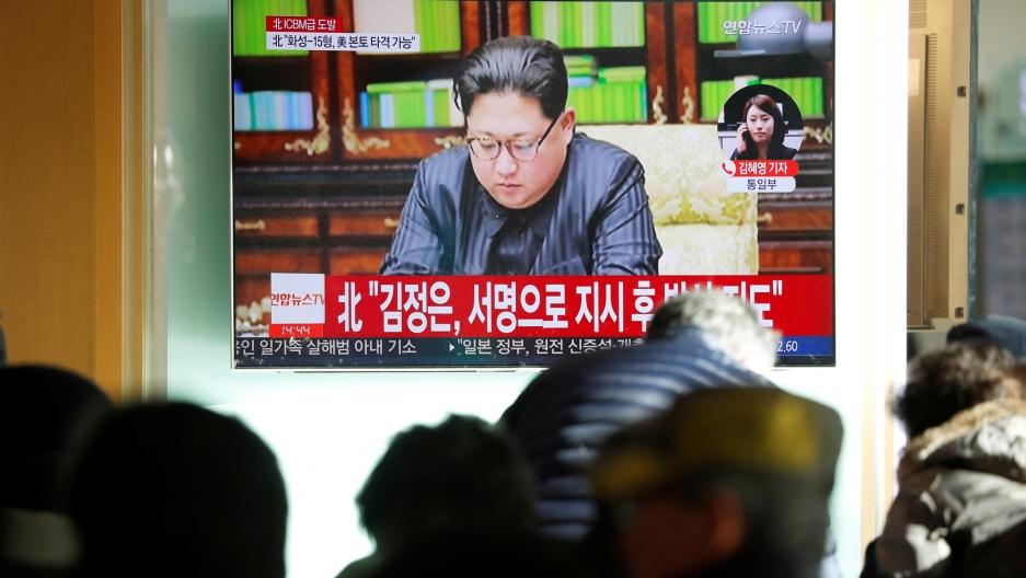 Several people out of focus are in the near ground with a TV monitor in the background showing Kim Jong-un.