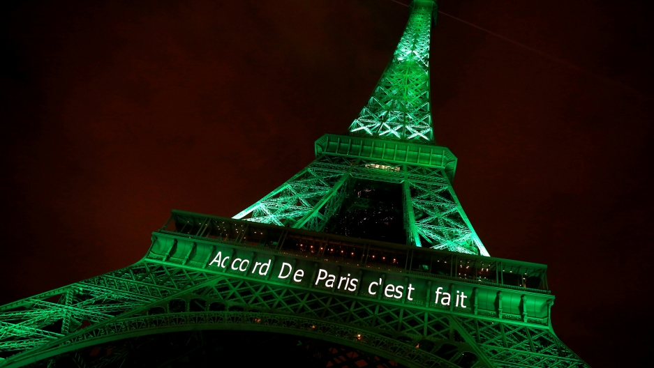 """The Eiffel tower is illuminated in green with the words """"Paris Agreement is Done"""