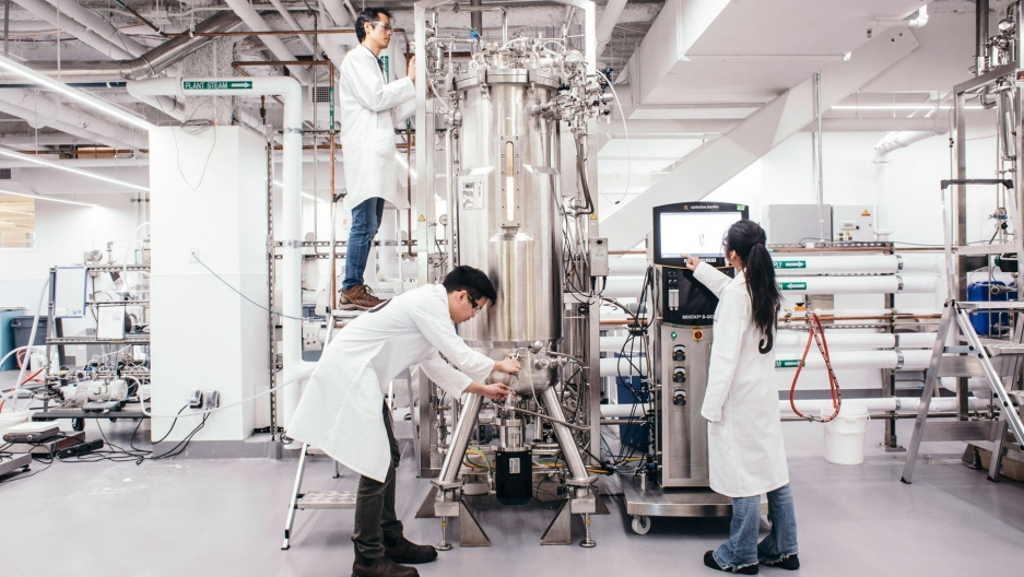 Three scientists in white lab coats stand around a tall metal container while taking measurements.
