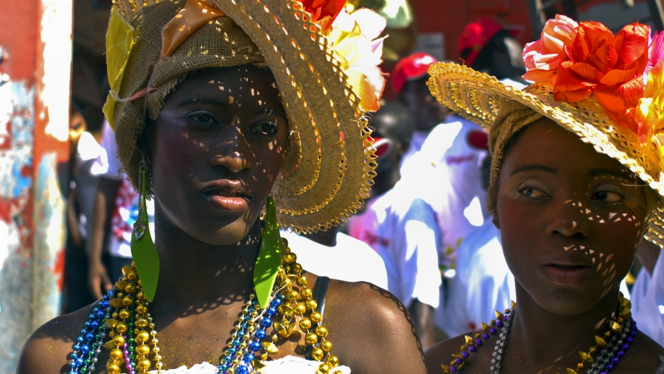 Women wear costumes as they take part in Carnaval in Jacmel, Haiti. The similarity between Carnaval and Mardi Gras in New Orleans is just one connection the two places share.