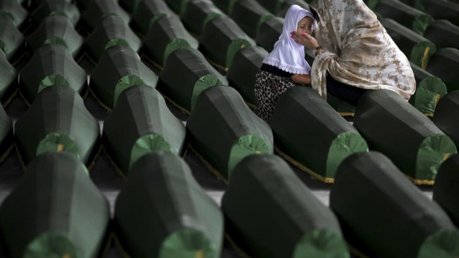 A Bosnian Muslim woman and child cry near the coffin of their relative, which is one of the 175 coffins of newly identified victims from the 1995 Srebrenica massacre, in the Potocari Memorial Center, near Srebrenica, July 10, 2014.