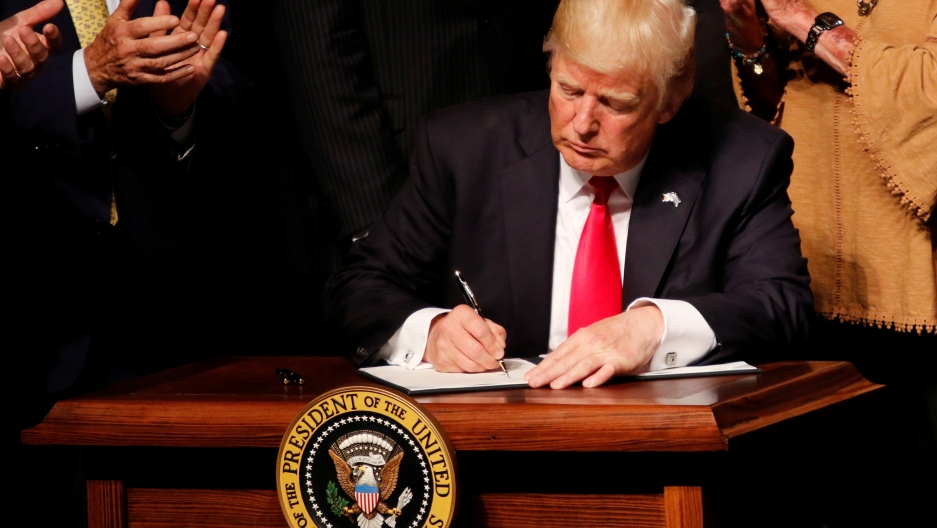 US President Donald Trump signs a document after announcing his Cuba policy