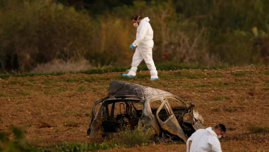Forensic experts walk in a field after a powerful bomb blew up a car and killed investigative journalist Daphne Caruana Galizia