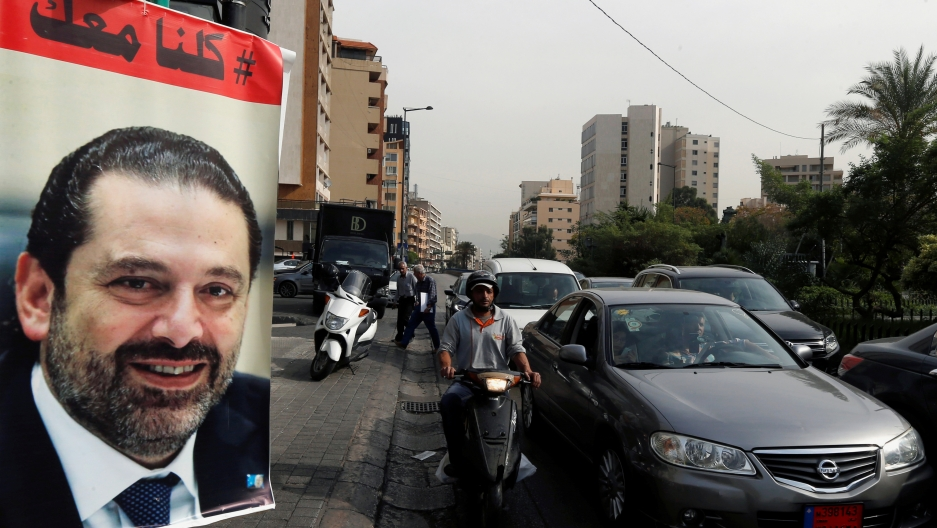 Cars pass next to a poster depicting Saad Hariri, who has resigned as Lebanon's prime minister, in Beirut