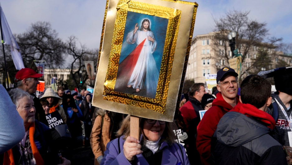 """An anti-abortion marcher carries a picture of Jesus Christ during a rally at the Supreme Court during the 46th annual """"March for Life"""" in Washington, D.C. on January 18, 2019."""
