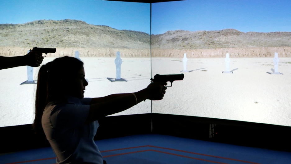 An Arab Israeli police recruit takes aim with her gun towards a screen displaying targets