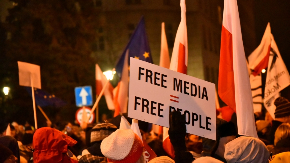 Polish protestors demonstrate their opposition to new restrictions for media in front of the parliament building in Warsaw, Poland.