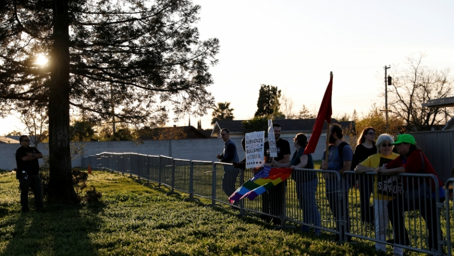 Line of protesters on lawn behind fence, with police officer near tree at edge of photo