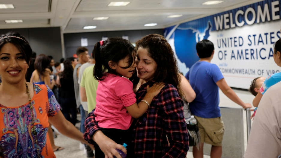 Zarfishan Zahid (L) smiles as Sana Tahir (R) holds Malaika Noman, 3, as the child arrives in the United States after a federal judge ruled in July that President Trump's temporary ban on travelers from six Muslim-majority countries cannot stop grandparent