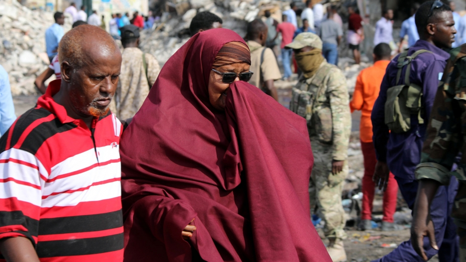 A woman holds her hand over her face and clutches the arm of a man next to her as they walk through the destroyed shopping district in Mogadishu.