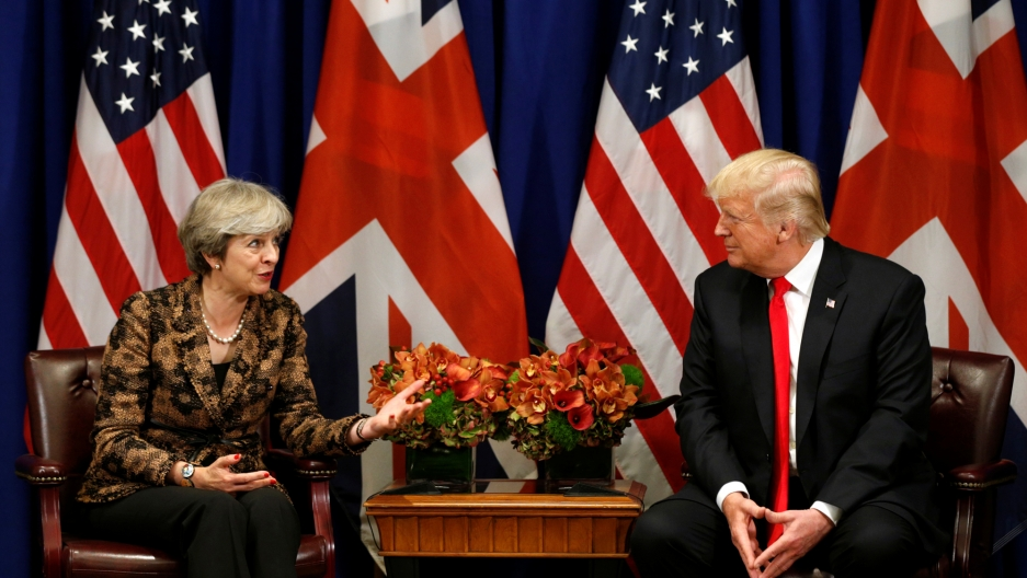 President Donald Trump sits across from Prime Minister Theresa in front of US and British flags.