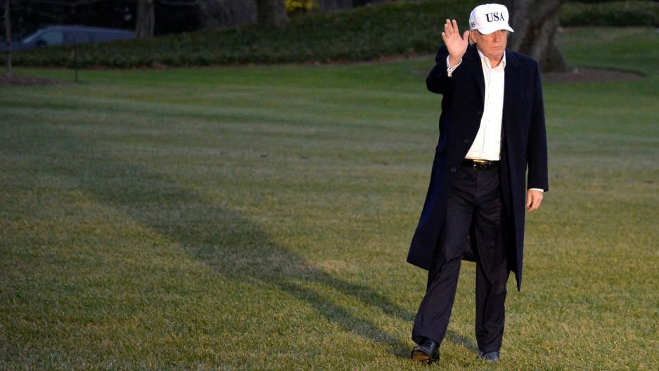President Trump, wearing a white baseball hat with the letters U.S.A. embroidered, waves to cameras while walking on the White House lawn