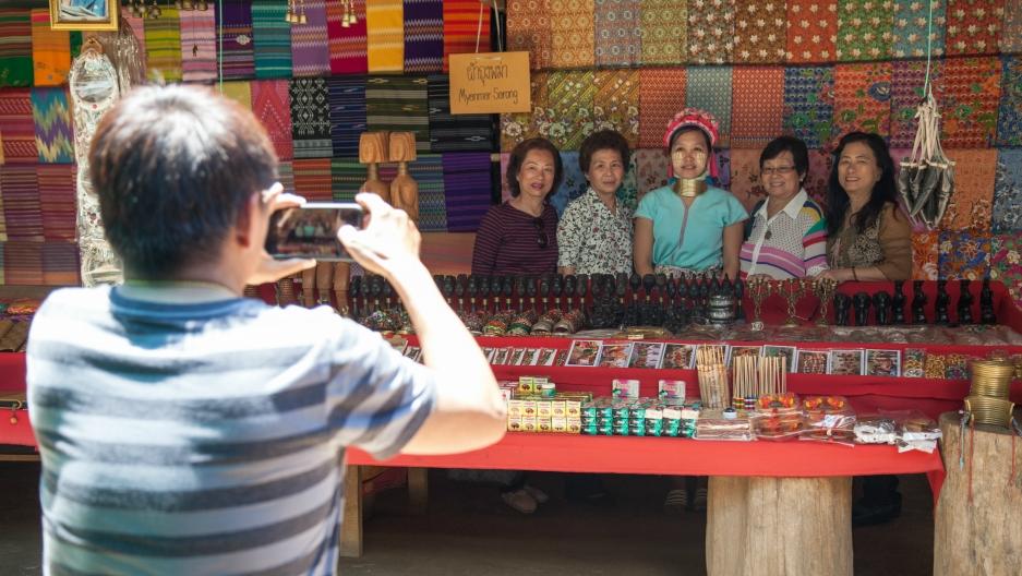 Thai tourists from Bangkok take a photo with one of the women at Huai Sua Tao.
