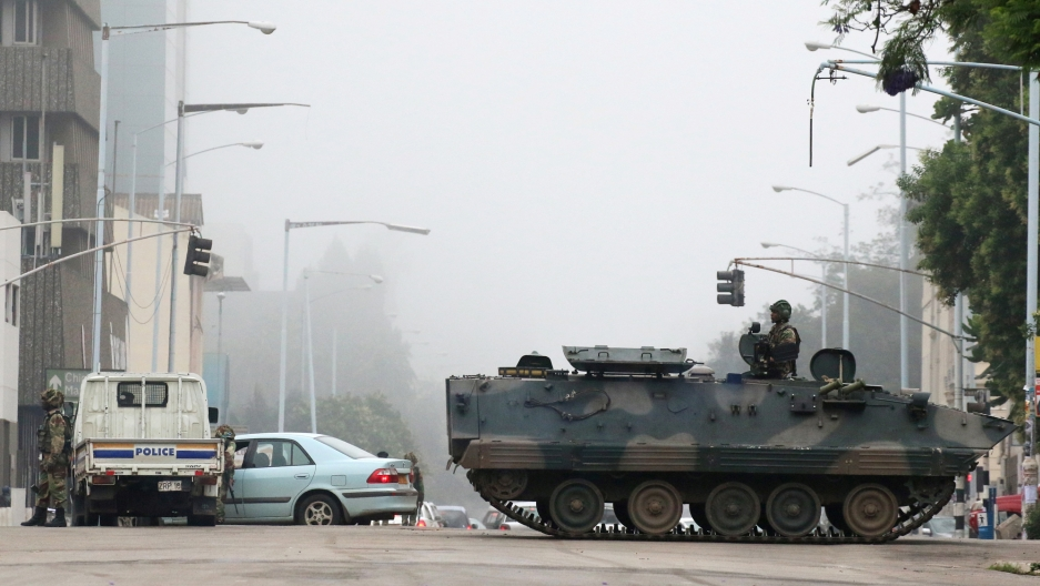 A tank with a soldier standing up on top is parked in the middle of the street in Harare, Zimbabwe,