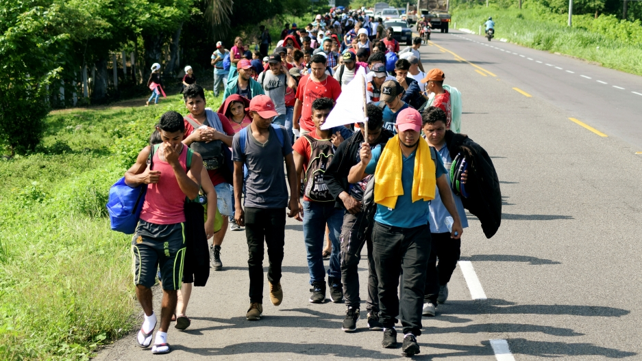A line of migrants carries bags and walks on a road