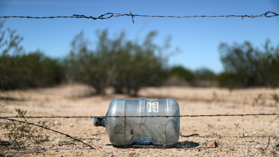 An empty water bottle lays on the dirt behind a string of barbed wire