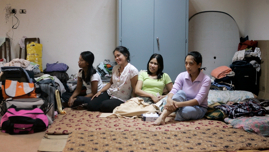 Four women sit crosslegged on the floor of a windowless room. Around them are suitcases and bedding. A baby is wrapped in a blanket nearby.