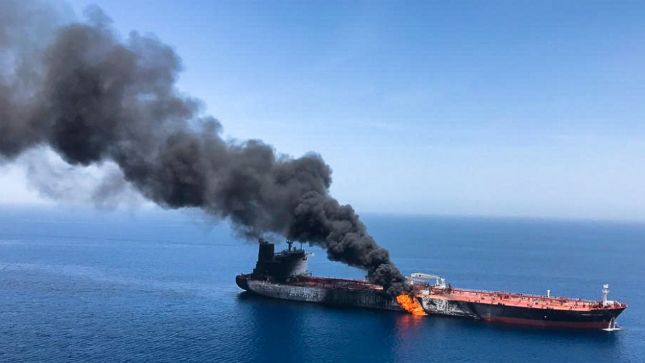Smoke billows from an open fire it the side of a massive oil tanker out at sea