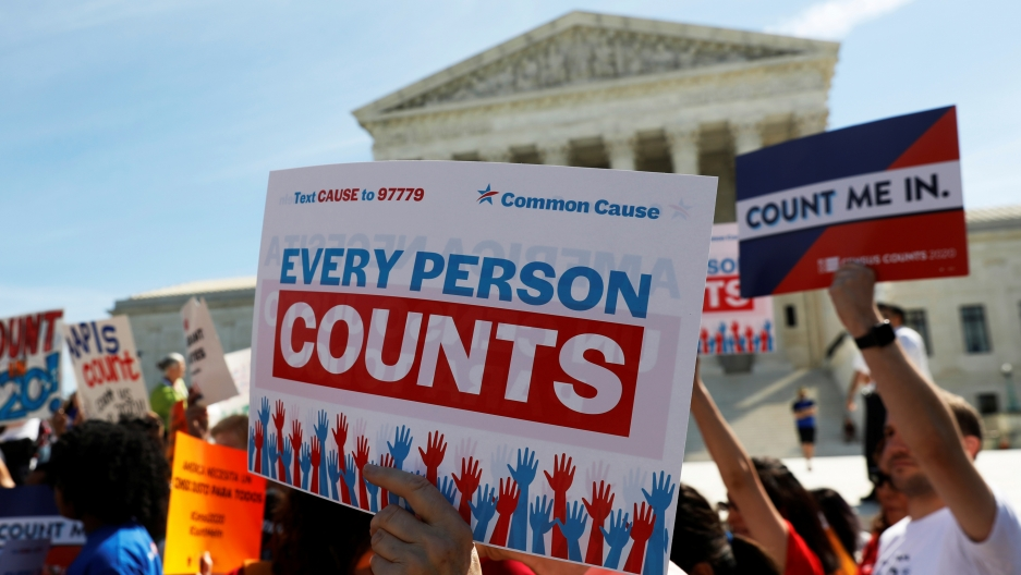 "Protesters stand outside court with sign that reads ""Every person counts"""