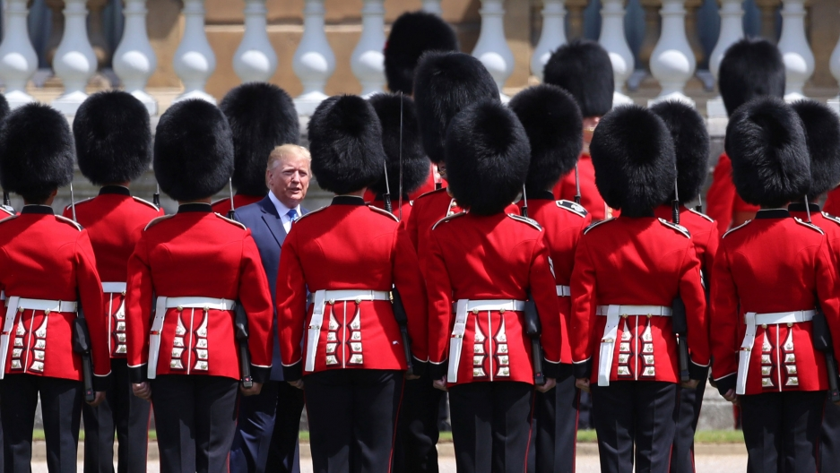 Donald Trump is shown standing among more than a dozen of the Royal honor guard dressed in traditional red uniforms and tall black hats.
