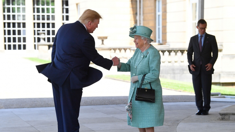Britain's Queen Elizabeth II greets US President Donald Trump are shown facing each other shaking hands.