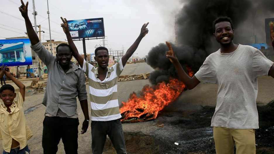 Sudanese protesters gesture near burning tires used to erect a barricade on a street, demanding that the country's Transitional Military Council handover power to civilians.