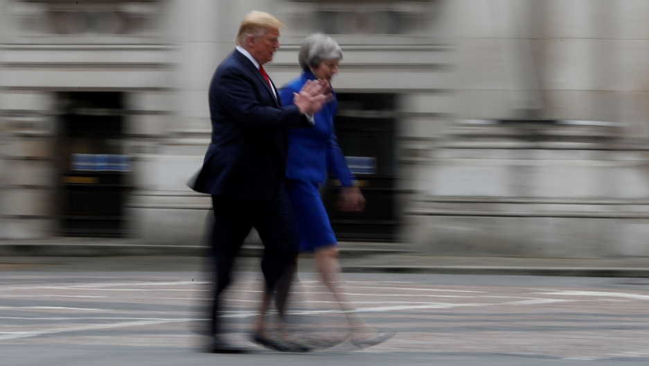 US President Donald Trump is shown wearing a dark blue suit and Britain's Prime Minister Theresa May is shown wearing a light blue suit as they are walking.