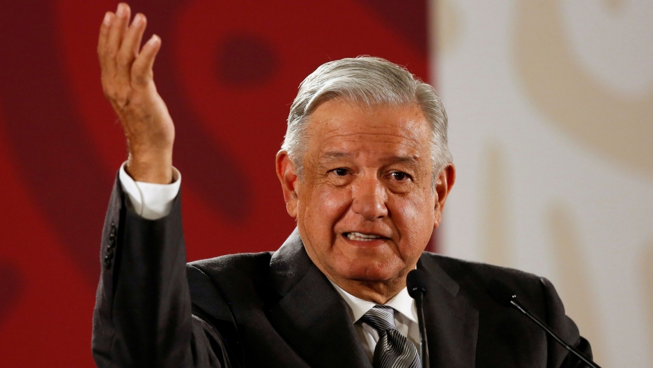 Mexico's President Andrés Manuel López Obrador is shown with his right hand raised in the air and a red and white background.