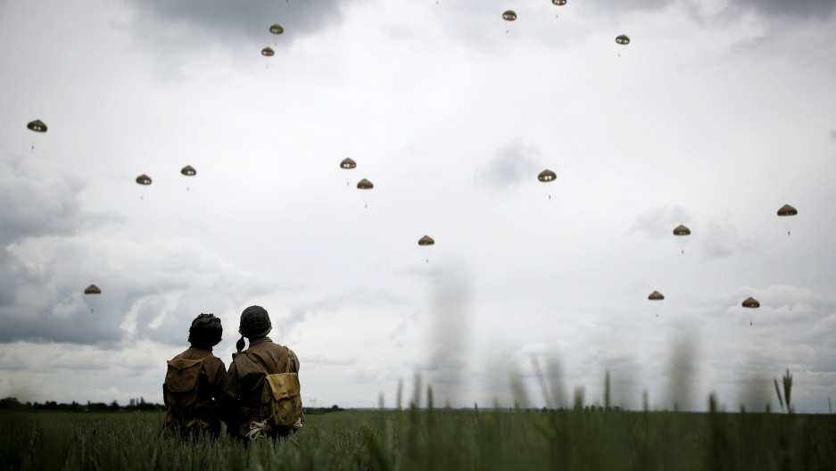 More than a dozen parachutes are shown in the sky with two people dressed in WWII military uniforms in the nearground.