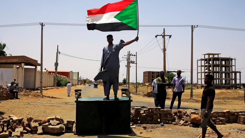A man stands on platform holding a Sudanese flag.