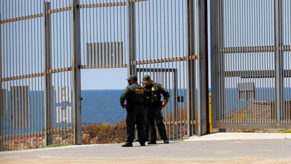 Two US Border Patrol agent are seen standing in uniform with their hands on their hips.