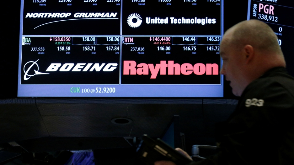A man is shown in soft focus in the nearground with a stock trading electronic board in the background.