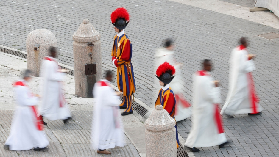 Several Catholic priests wearing white robes are shown walking past two guards in traditional striped uniforms.