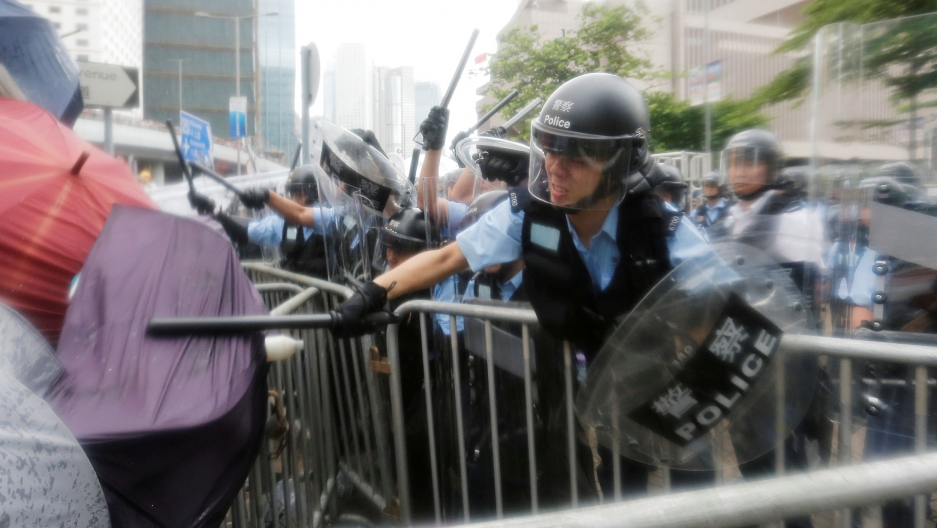 A police officer is shown with a helmet and clear face mask down, striking a person with an umbrella with his batton.