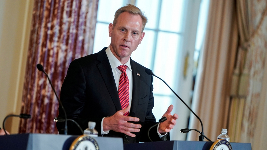 Acting US Secretary of Defense Patrick Shanahan is shown standing behind a podium with a microphone, looking to his right.