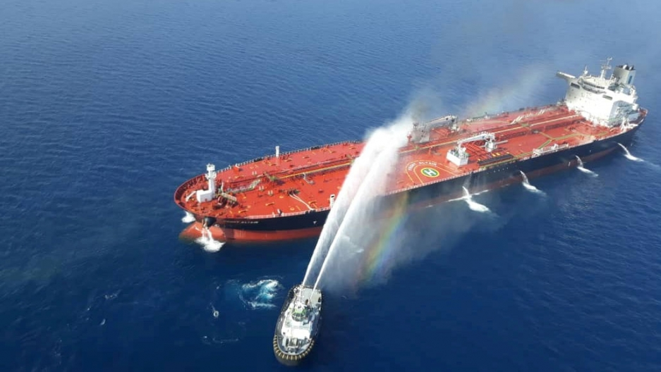 An oil tanker is shown from above with a red deck and being sprayed by water by a second, adjacent boat.