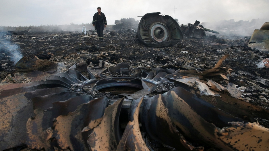 A man is shown in the distance walking amongst the smoldering rubble of a crashed airplane.