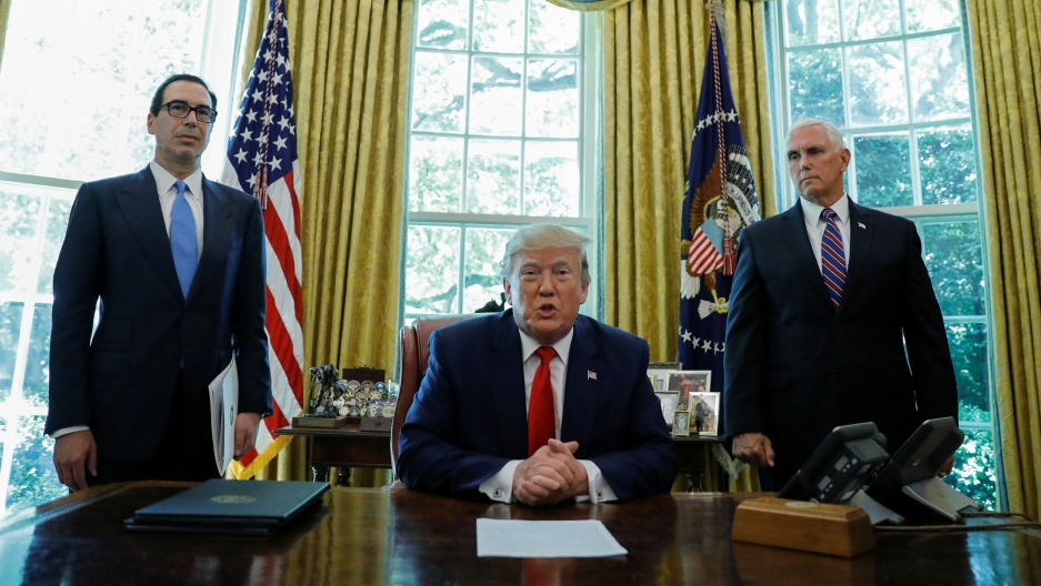 US President Donald Trump is shown sitting at a large wooden desk with his hands folded and wearing a blue suit and red tie.