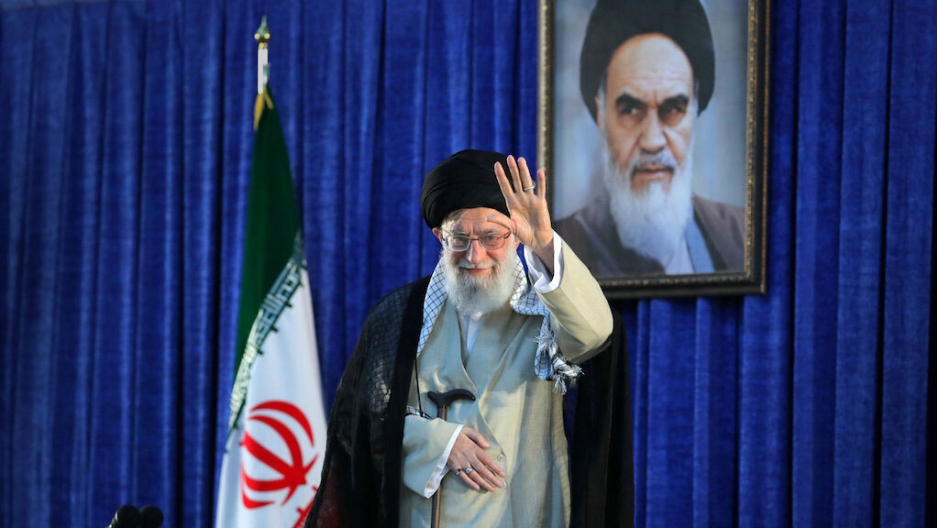 Iran's Supreme Leader Ayatollah Ali Khamenei is shown waving while standing next to an Iranian flag.