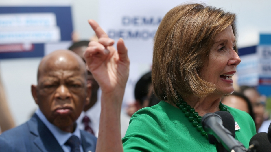 US House Speaker Nancy Pelosi is shown speaking behind microphones with her right hand raised pointing in the air.